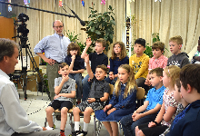 News anchor interviews students and their teacher in their classroom