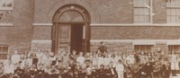 Students outside school building in the 1800s