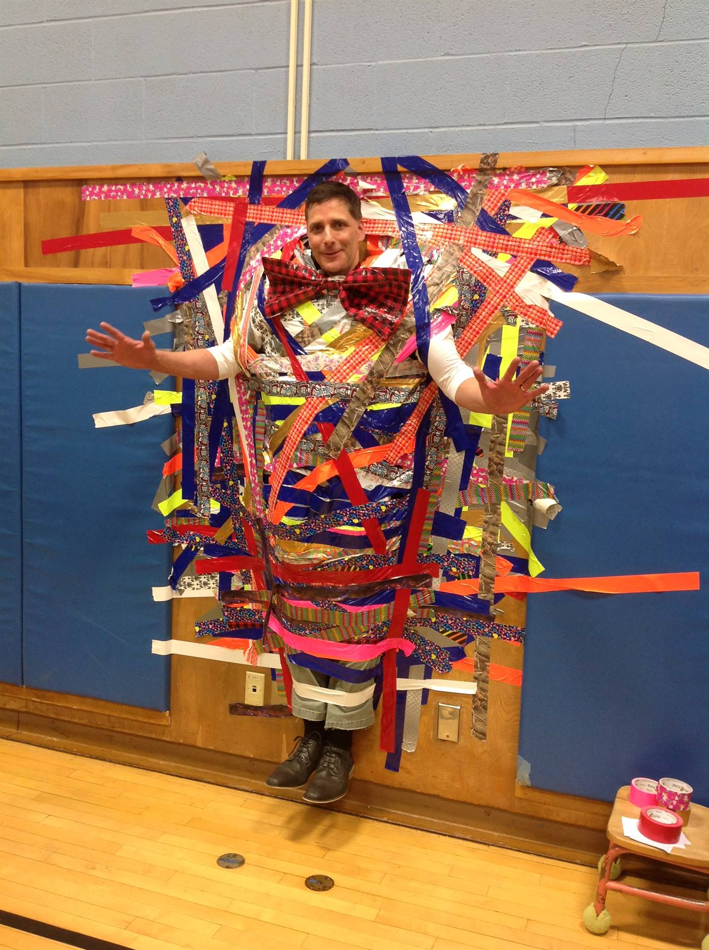Principal Mr. Baskin duct-taped to the wall following hurricane-relief fundraising efforts