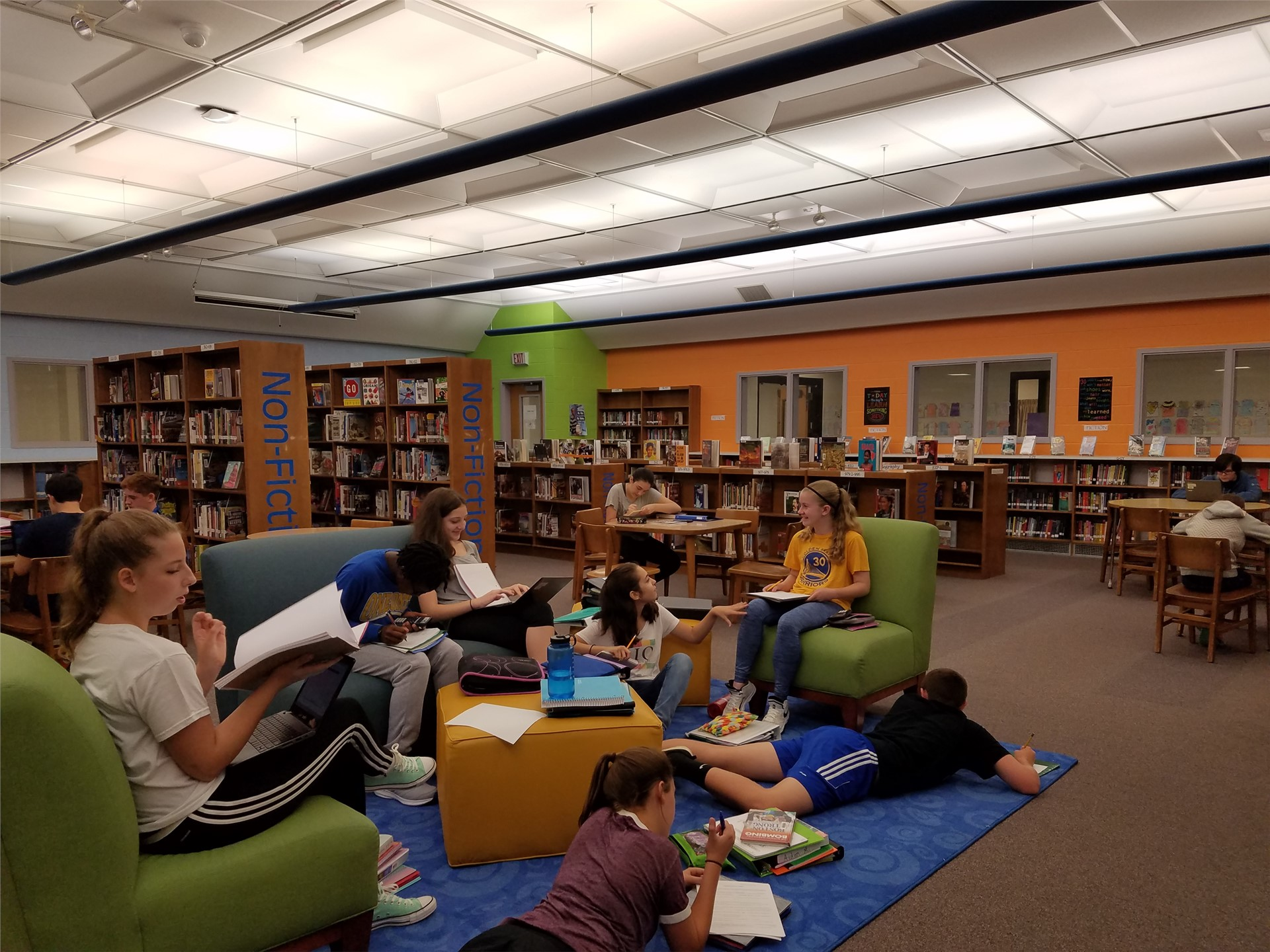 Students hanging out on comfortable furniture in the library