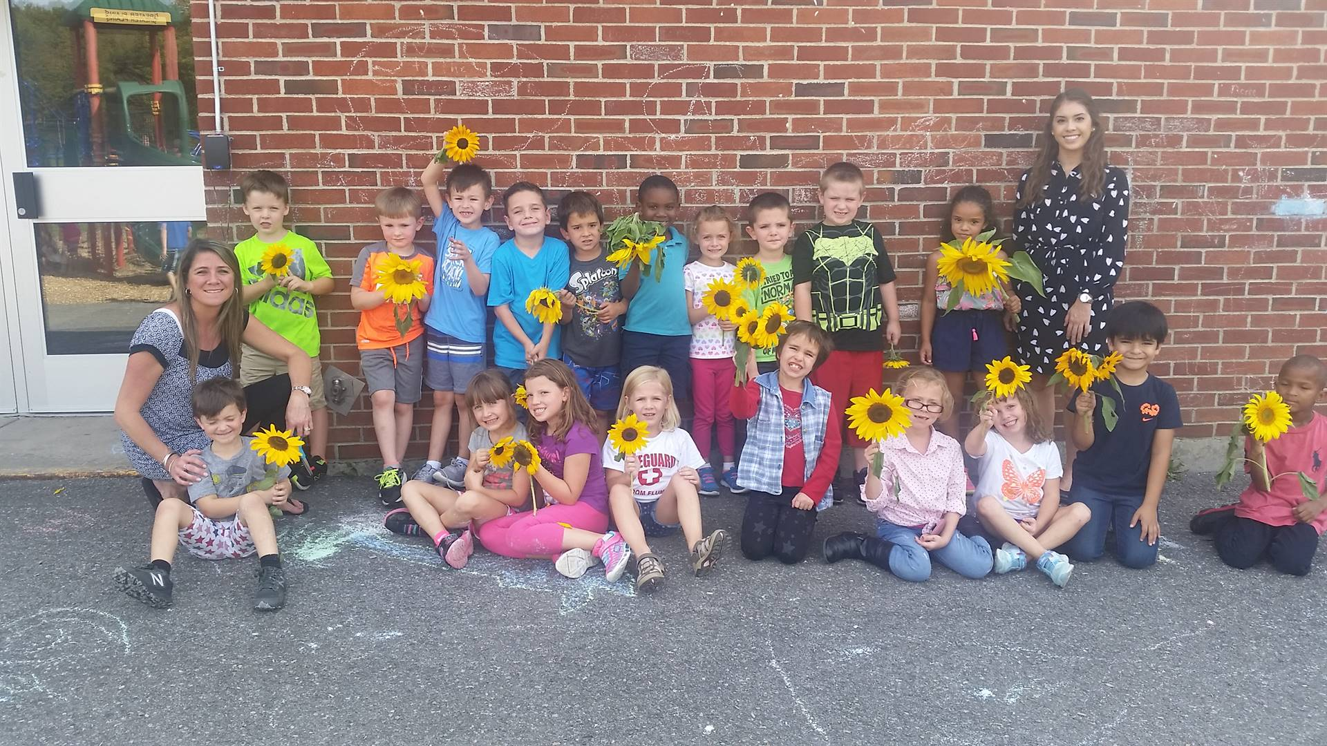 Students show sunflowers from the school garden