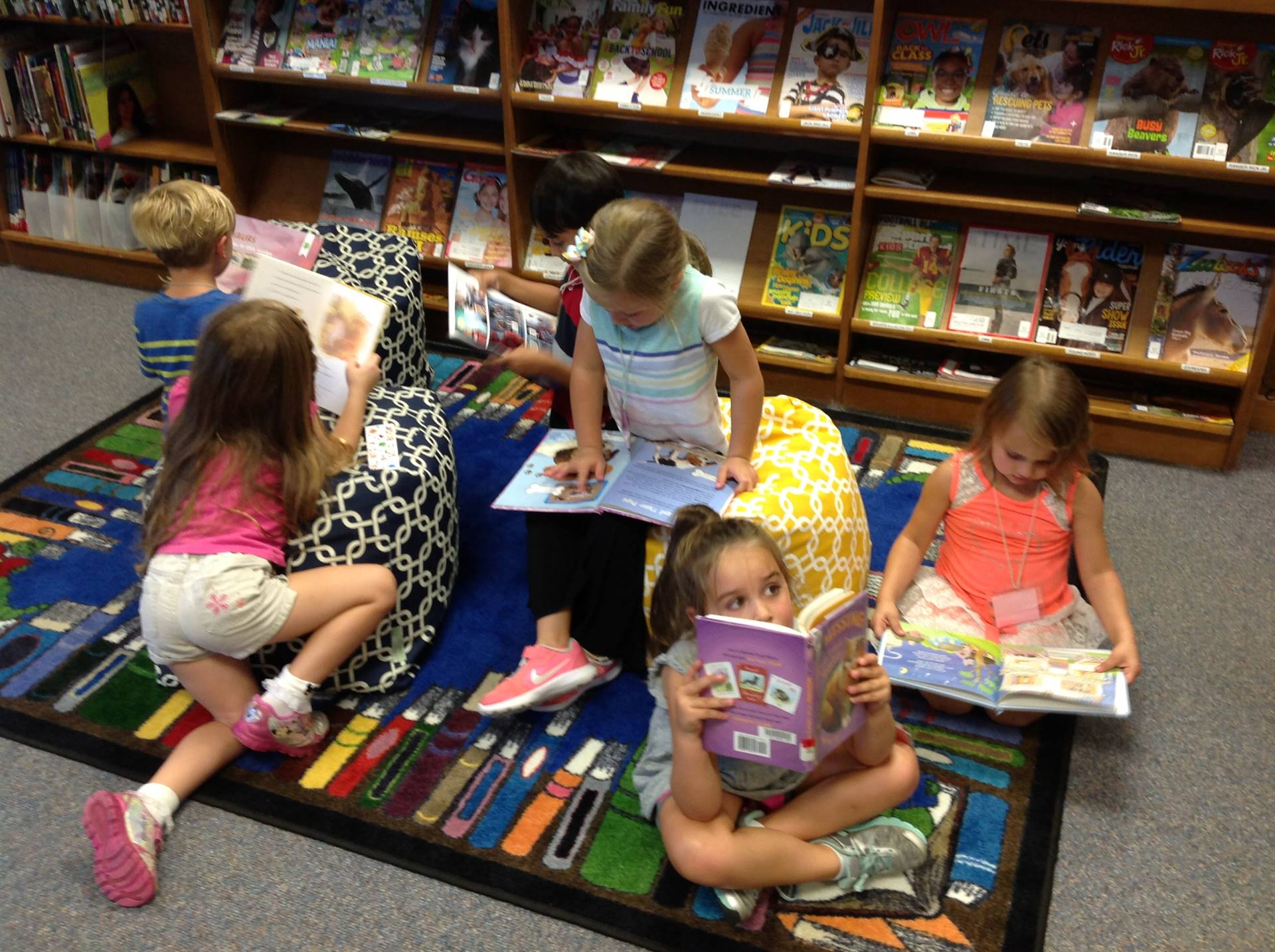 Kindergarteners look at books in the library