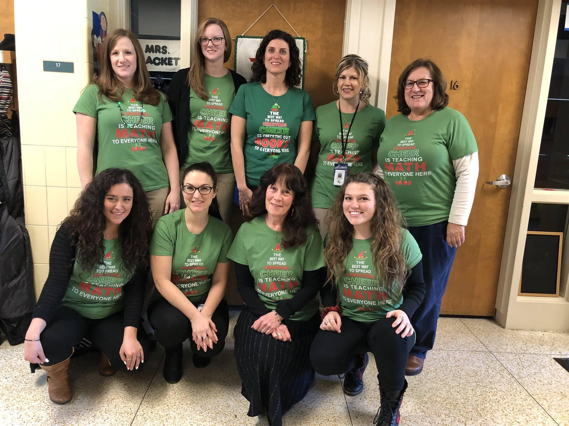 Teachers wearing matching green holiday shirts