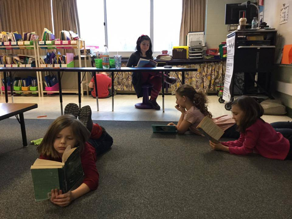 Students sit on floor and at table, reading