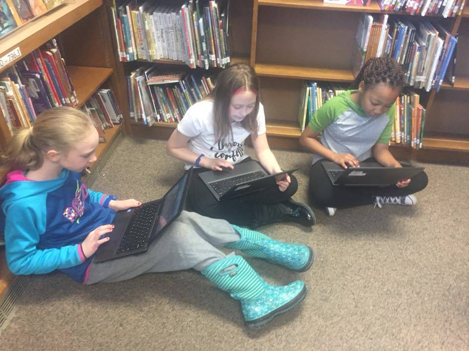 Students use Chromebooks seated on the floor