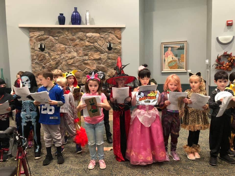 First graders on Halloween visiting a nursing home