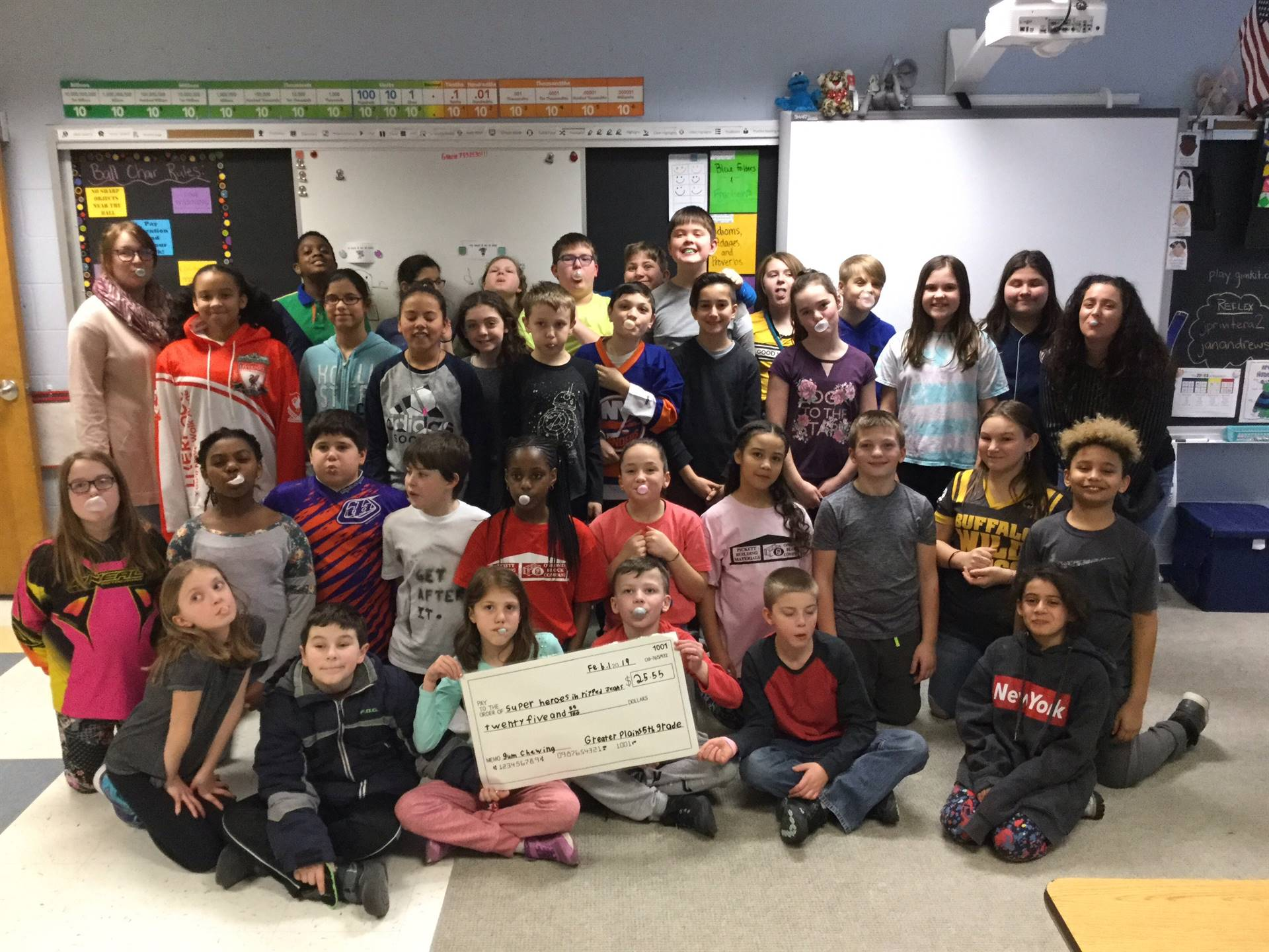 "GP 5th Graders hold up a ""check"" for $25.55 to donate for chewing gum"