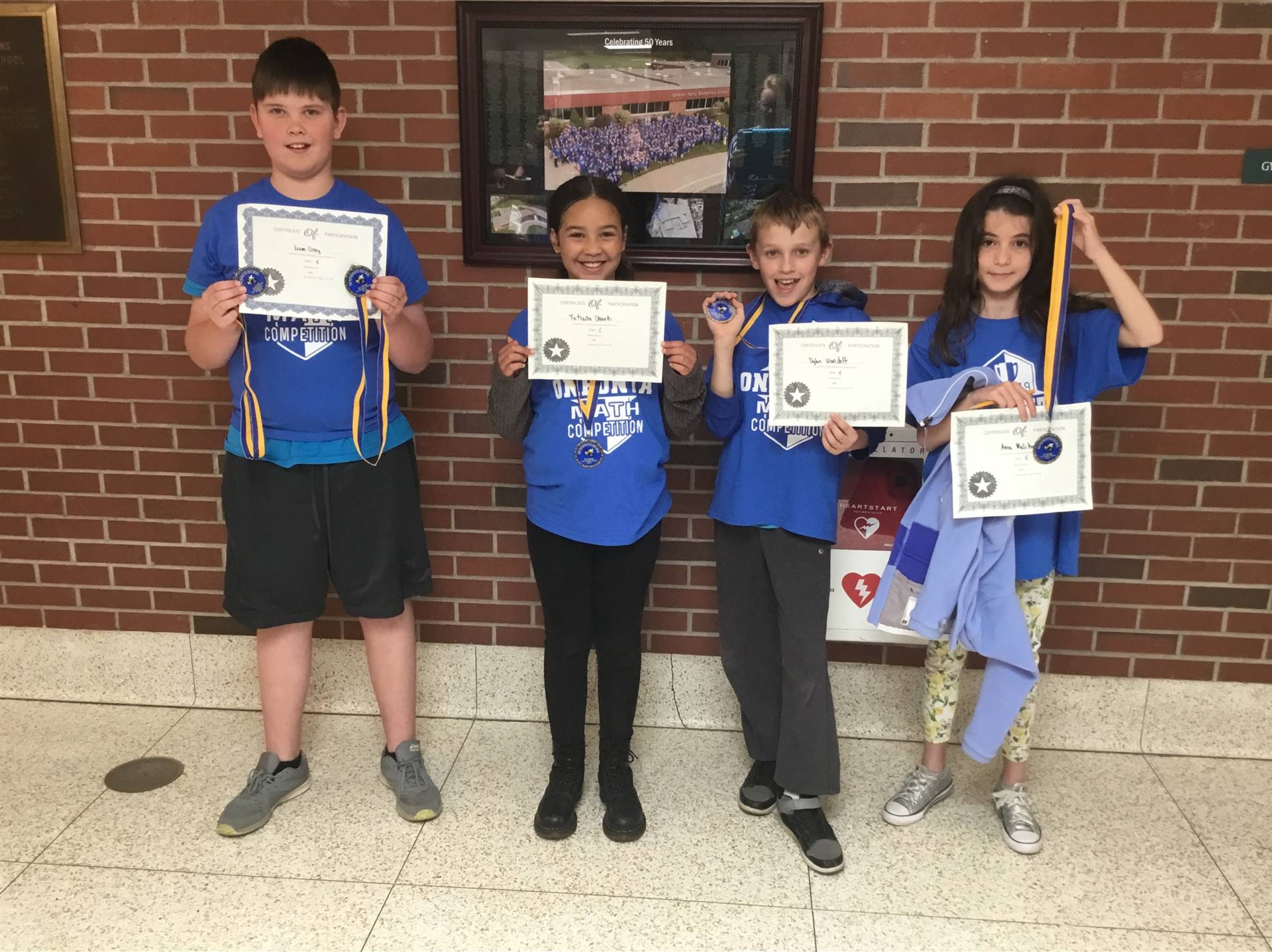 The Victorious Fifth Grade Math Bowl Participants hold up their medals and certificates