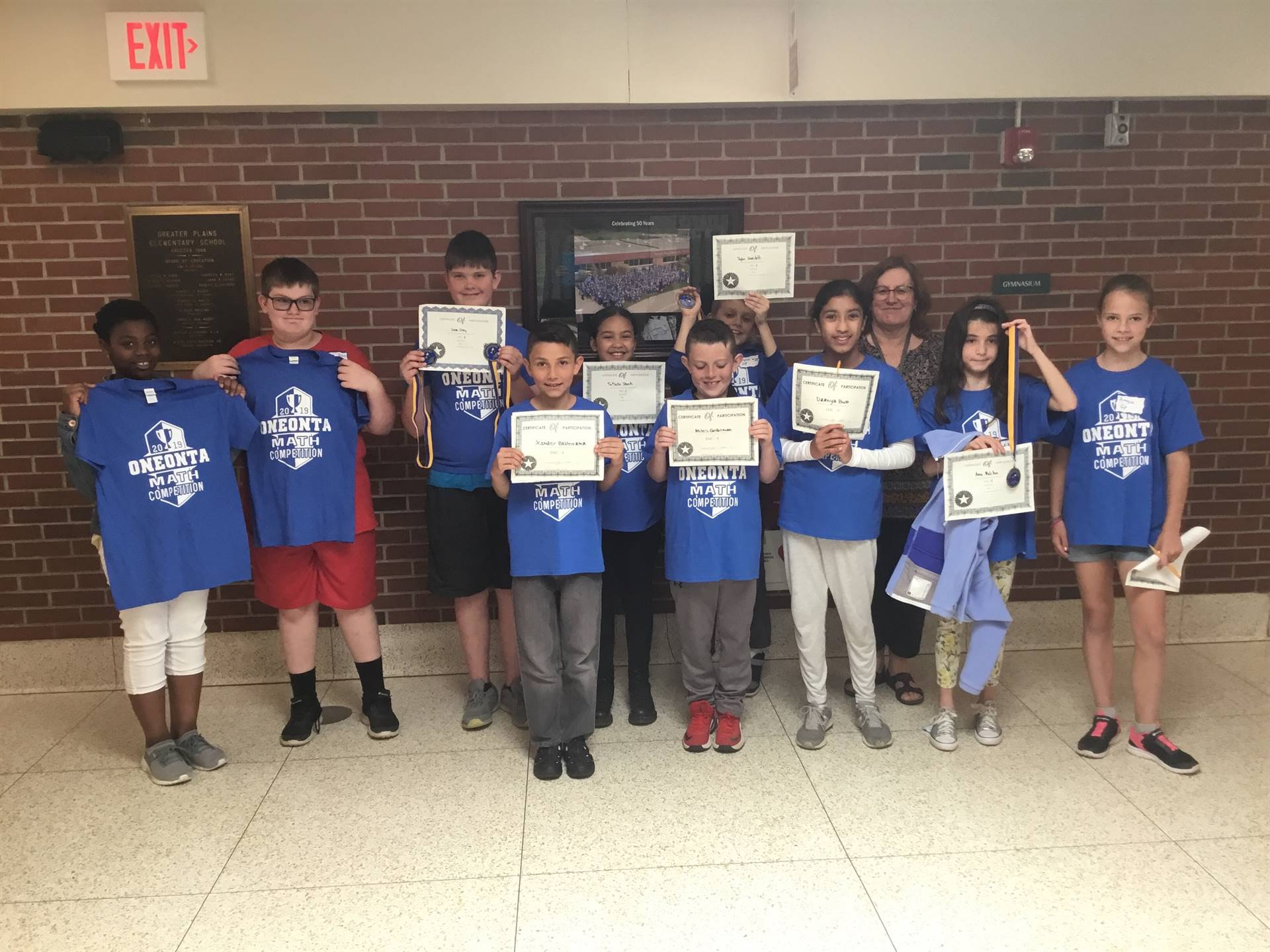 Fourth and Fifth Grade Math Bowl Participants hold up their medals and certificates