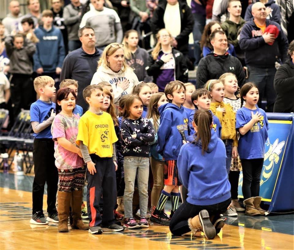 2nd graders sing the National Anthem at the basketball game