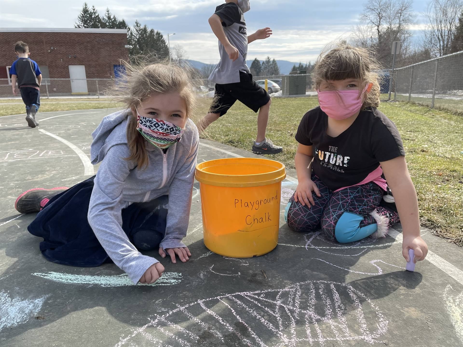 students drawing with sidewalk chalk
